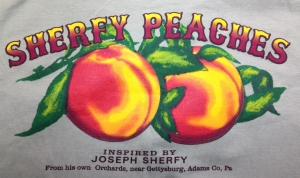 T-shirts, peach taffy, and aprons, adorned with the Sherfy Peach Orchard logo, are now for sale at the Gettysburg Visitors Center.